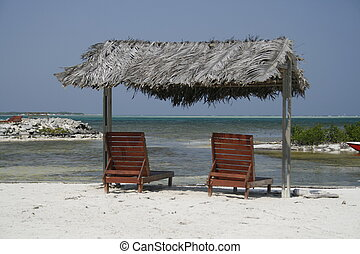 two wooden reclining chairs under a thatched roof at the caribbean ocean in Bonaire