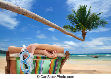 Tropical View - Woman in deckchair on tropical beach with...