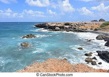 Black stone beach with aqua tropical waters in Aruba.