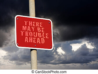 Trouble ahead sign against a dark cloud background