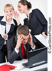 Photo of thinking boss in front of laptop while one of his employees whispering something to another woman