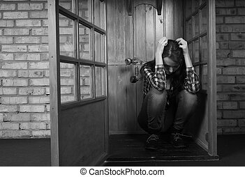 Troubled Woman Holding Head in Hands and Crouching in Public Telephone Booth