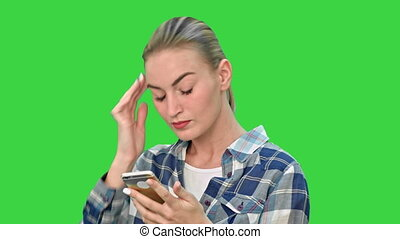 Troubled woman reading bad text news on phone touching her head in misery. Close up on a Green Screen, Chroma Key. 076. You can use it e.g. in your commercial video, business, medical presentation, broadcast video.