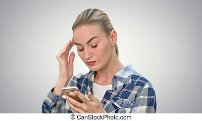 Troubled woman reading bad text news on phone touching her head in misery on white background.