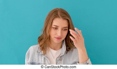 Pensive worried female in casual clothes looking down and pondering while standing against blue background in studio