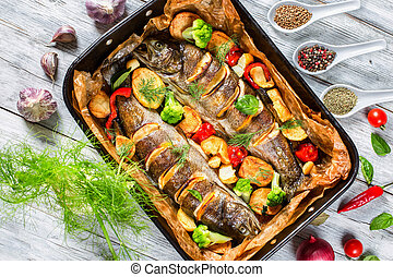 trout fishes baked with potatoes, broccoli, lemon, tomatoes