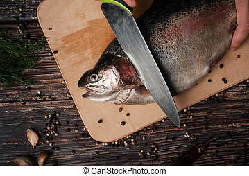 trout on the Board with a knife cutting it for cooking
