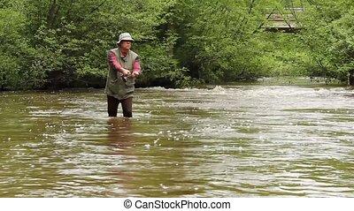 trout fisherman in a stream walking toward the camera
