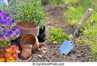 trowel planting in the dirt next to flowerpots in a garden
