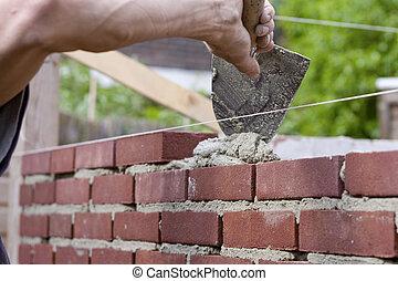 Trowel spreading cement on bricks - Construction of brick...
