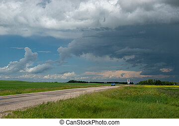 Truck approaching with looming storm clouds, Saskatchewan, Canada.