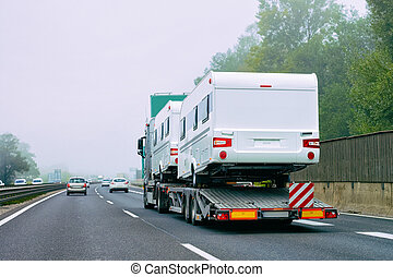 Truck carrier with motor homes rv on road of Slovenia