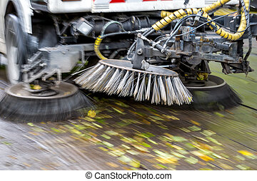 Truck cleaning street at autumn