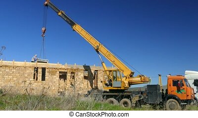 Truck crane stacks concrete slabs on unfinished house