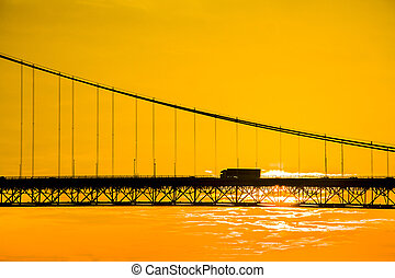 Truck crossing hanging bridge at sunset