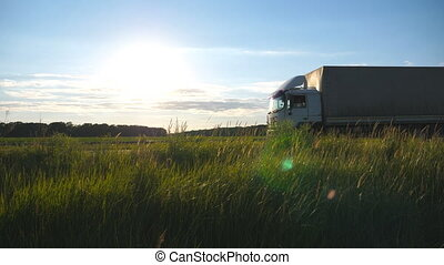 Truck driving on a highway with sun flare at background....