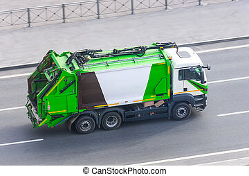 Truck for waste collection in residential areas of the city rides on the road.