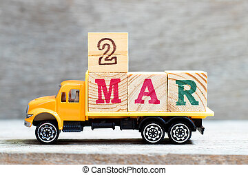 Truck hold letter block in word 2mar on wood background (Concept for date 2 month March)