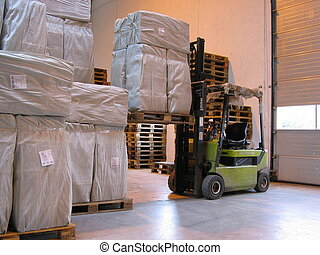 Truck lifting pallet - A truck lifting a pallet with white...