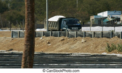 NHA TRANG/VIETNAM - MARCH 23 2018: Large truck loaded with salt pile drives along empty road against buildings and tropical forest on March 23 in Nha Trang