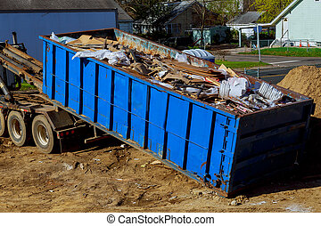 Truck loading a full skip recycling garbage waste management...