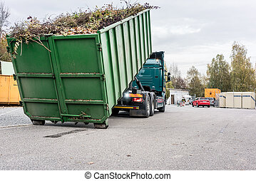 Truck loading container with waste green at recycling center...