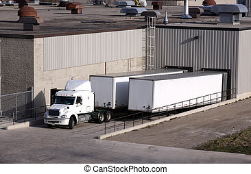 Truck Loading Dock - A transport truck getting loaded at a...