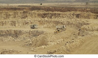 Truck loading in a quarry. Two trucks and excavator