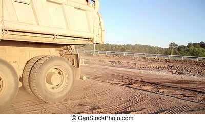 Truck moving backwards in the site and several visible truck tires everywhere. Truck maybe finding a good place to unload its item.