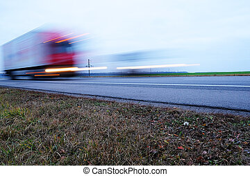 Truck on a hughway. Truck is blurred because of movement