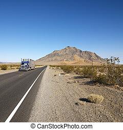 Truck on desert road.