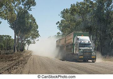 Truck on dusty dirt road - Semi-trailer road train carrying...