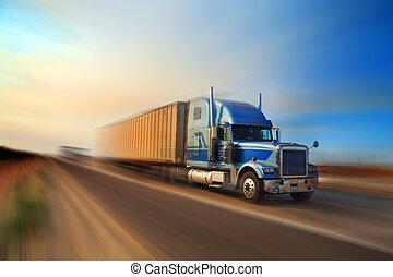 American truck speeding on freeway at sunset, motion blurred.