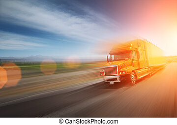 Truck speeding on freeway at sunset. Blurred motion.