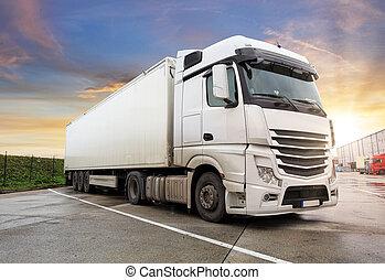 Truck on the asphalt road in rural landscape at sunset