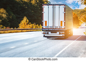 truck on the asphalt rural road on the sunset