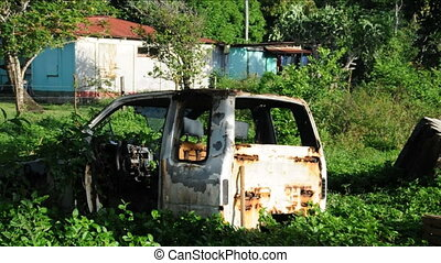 truck body rotting rusting in jungle with coconut tree and native houses Corn Island Nicaragua Central America