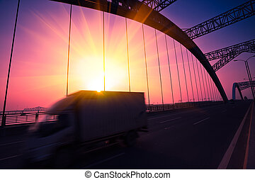 truck speeding through a bridge at sunset, motion blur.