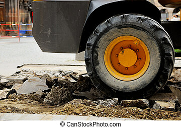 Truck tire on a broken asphalt at construction site in urban environment