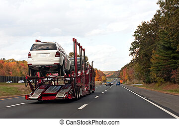 An automotive car carrier truck driving down the highway with a full load of new vehicles.