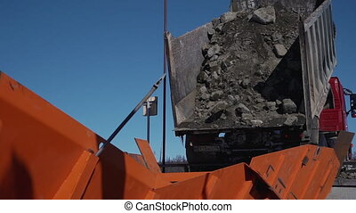 Truck unloading rocks working on construction site of oil factory in winter.