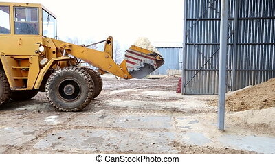 Truck unloading sawdust in territory of sawmill - View on...