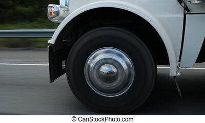 Closeup of a truck wheel on the highway. Reflection of car in truck hubcap.