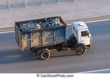 Truck with a metal container full of garbage goes down the highway to the dump.