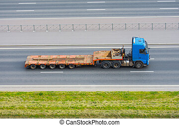 Truck with a trailer and an empty long platform rides in the city on the highway.