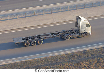 Truck with an empty long trailer without cargo, driving on the highway, top above view.