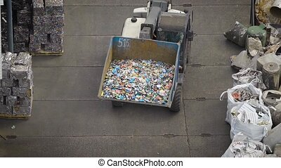 Truck with big scoop sorting trash on yard of recycling...