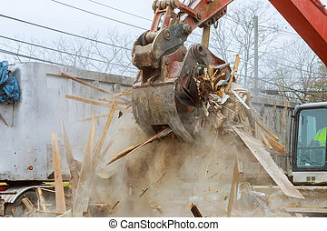 Truck with excavator loads construction waste on a dump truck