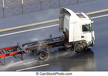 Truck with trailer and an empty orange long platform driving on wet asphalt after rain.