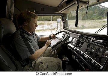 A Truck Driver updates his logbook in a modern semi truck cab.